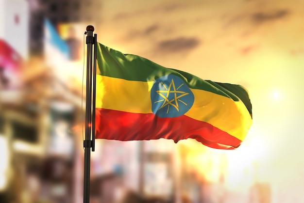 Ethiopië vlag tegen stad wazige achtergrond bij zonsopgang achtergrondverlichting