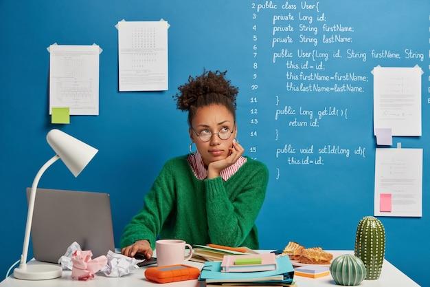 Etniciteit vrouw poseert op werktafel, kijkt weg, wordt afgeleid van het werk, denkt na over iets terwijl op moderne laptop werkt