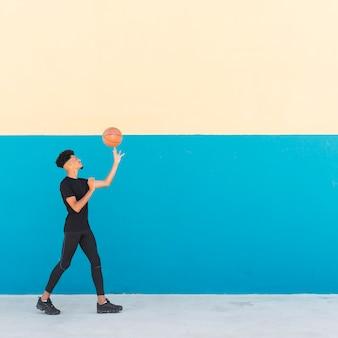 Etnisch mannelijk spinnend basketbal op vinger