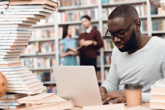 Etnische afro-amerikaanse man omringd door boeken in de bibliotheek. de student gebruikt laptop en drinkt koffie.