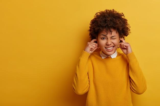 Etnische dame verknoeit ogen, klaagt over luide muziek, stopt oren