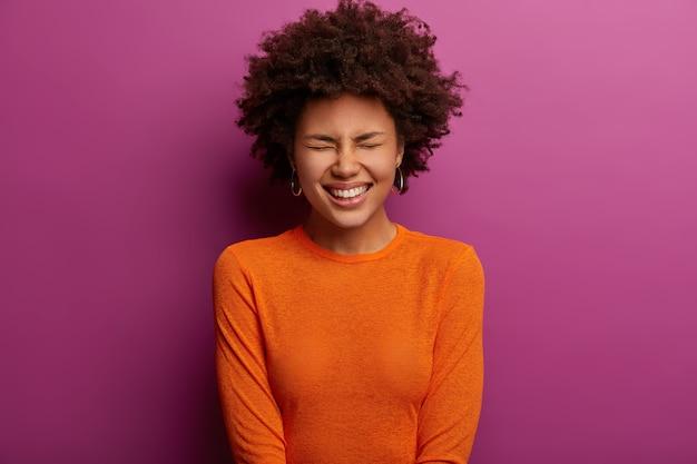Etnische dolgelukkige jonge vrouw lacht om iets positiefs, sluit de ogen en giechelt vrolijk, gekleed in een oranje trui, hoort grappige grappen, poseert tegen een levendige paarse muur. emoties concept
