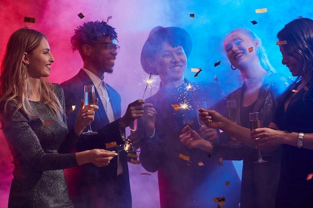 Etnische groep mensen vieren in smoky nightclub