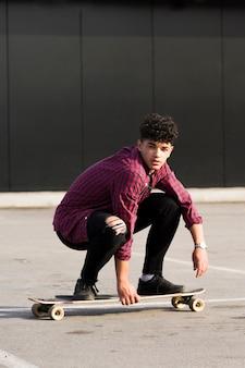 Etnische hipster in geruit hemd paardrijden skateboard squatting