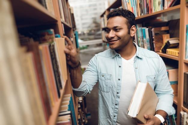 Etnische indiase student in boek gangpad van de bibliotheek