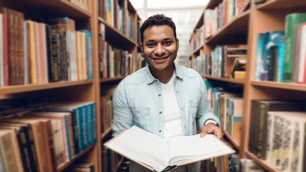 Etnische indische gemengde rasstudent in boekdoorgang van bibliotheek.