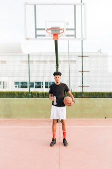 Etnische jonge man met basketbal aan het hof