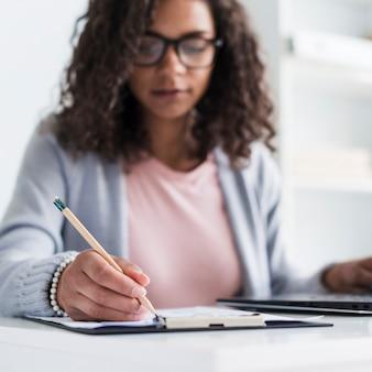 Etnische jonge vrouw schrijven op klembord