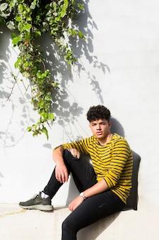 Etnische krullende man zit in de buurt van muur met groene planten