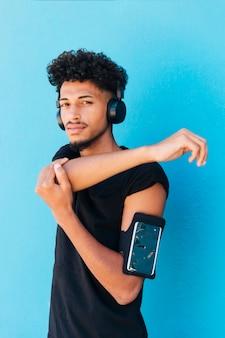 Etnische man die zich uitstrekt en naar muziek luistert met telefoonhoesje op arm
