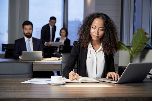Etnische onderneemster die in modern bureau werkt