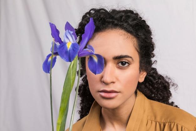 Etnische romantische brunette met boeket bloemen