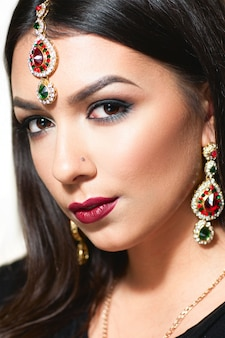 Etnische schoonheid. oosterse glimlachende vrouw met gouden juwelen