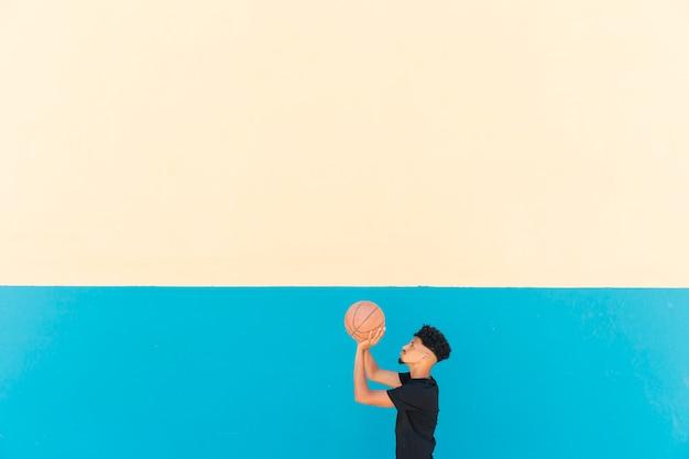 Etnische sportman die basketbal voorbereidingen treft te werpen