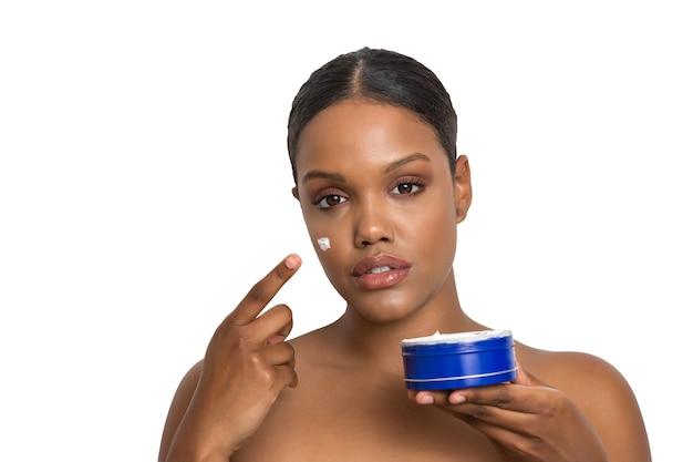 Etnische vrouw die crème op het gezicht aanbrengt