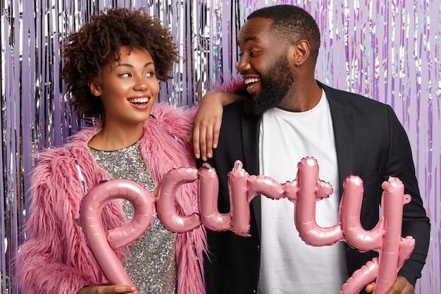 Etnische vrouw en man kijken elkaar vrolijk aan, hebben samen vreugde op het afscheidsfeestje