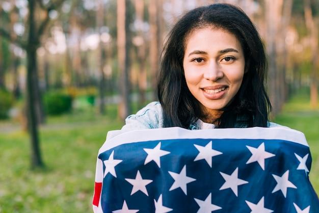 Etnische vrouw gewikkeld in amerikaanse vlag