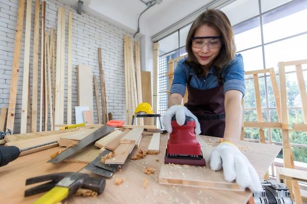 Etnische vrouw in schort en bril die timmerhout op tafel polijst terwijl ze in professionele schrijnwerkerij werkt