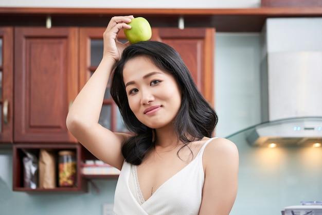 Etnische vrouw met appel op het hoofd