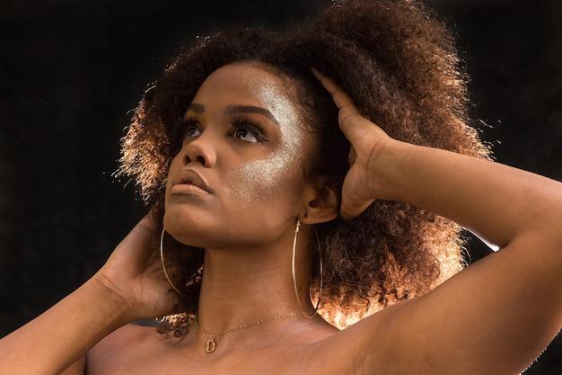 Etnische vrouw met trendy make-up wat betreft haar
