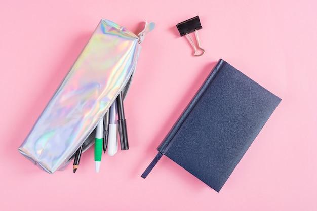 Etui met pennen en potloden, notitieblok op een roze.