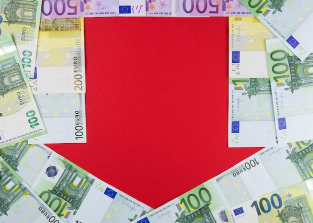 Eu-valuta van verschillende religies op een rode achtergrond in de vorm van een pijl-omlaag