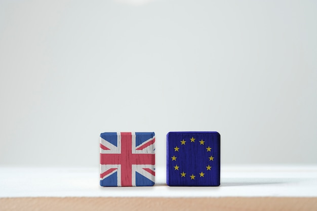 Eu-vlag en brits vlagscherm op houten kubiek. het is een symbool van de britse behoefte om brexit te verlaten of te bellen vanuit de zone van de europese unie.