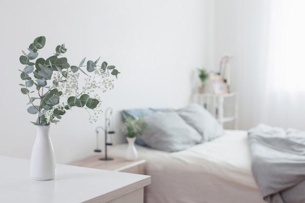 Eucalyptus en gipskruid in vaas in witte slaapkamer