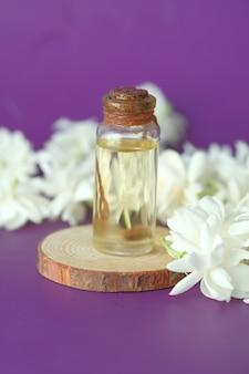 Eucalyptus etherische oliën in een glazen fles en bloem op paars oppervlak
