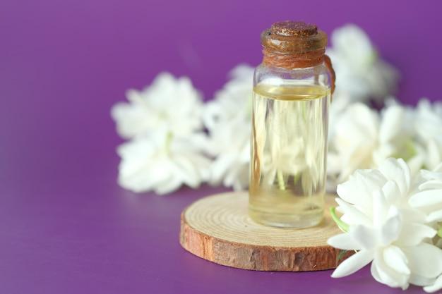 Eucalyptus etherische oliën in een glazen fles en bloem op paarse achtergrond