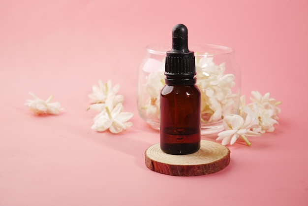 Eucalyptus etherische oliën in een glazen fles en bloem op roze achtergrond