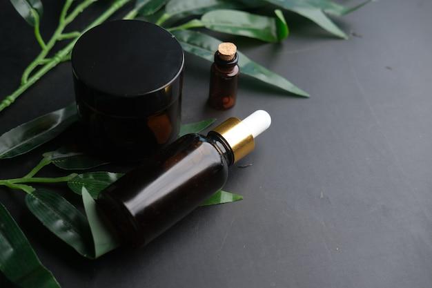 Eucalyptus etherische oliën in een glazen fles met groen blad op zwarte tafel