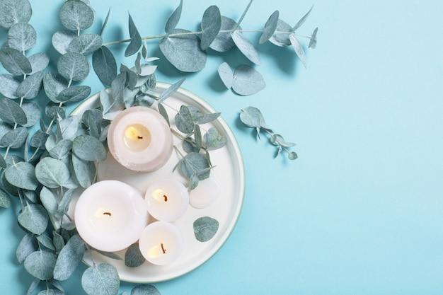 Eucalyptusbladeren en brandende kaarsen op blauwe achtergrond