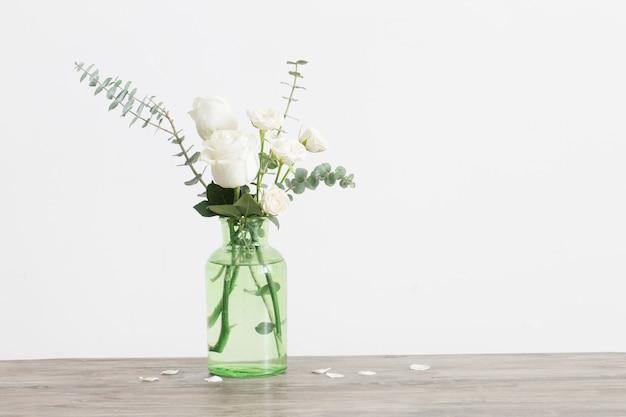 Eucalyptustakjes en rozen in glasvaas