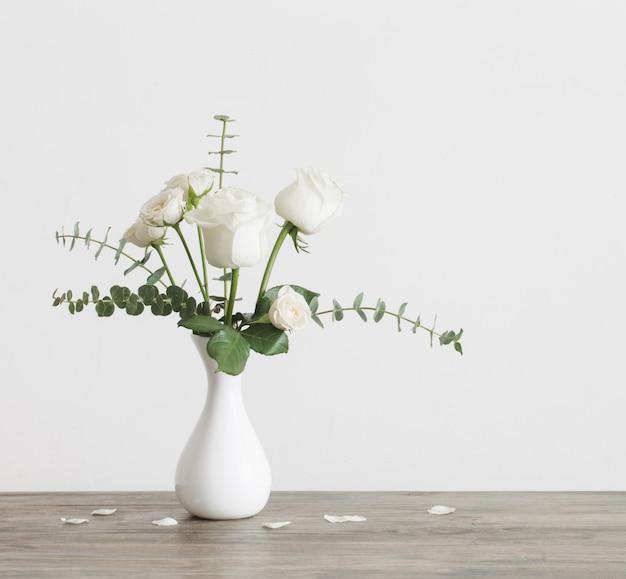 Eucalyptustakjes en rozen in vaas op witte oppervlakte