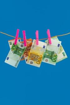 Euero geld op touw wasknijper op blauwe achtergrond