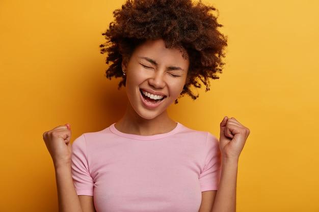 Euforische krullende vrouw maakt ja-gebaar, balt vuisten, opgewonden door goed nieuws, viert de overwinning, heeft een dolgelukkige uitdrukking, kreeg een prijs, kantelt het hoofd, poseert en gebaart tegen de gele muur