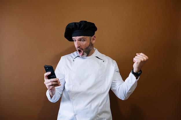 Euforische mannelijke chef-kok met behulp van een smartphone