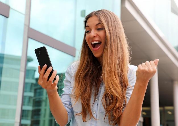 Euforische zakenvrouw kijken naar haar slimme telefoon en winnaar gebaar buiten tonen