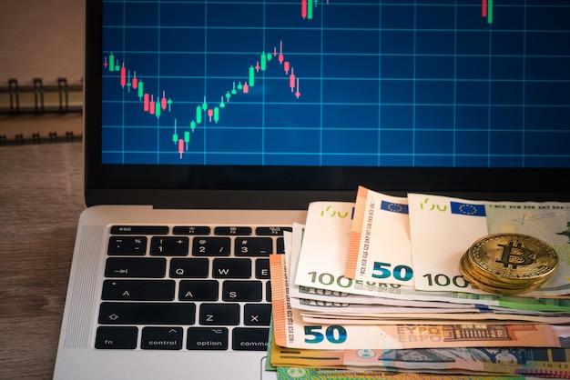 Eur-bankbiljet met bitcoin en monitor, euro bankbiljet over toetsenbord