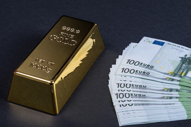 Euro contant geld en goudstaaf op zwart