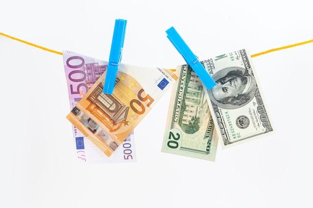 Euro- en dollarsbankbiljetten bevestigd met wasknijpers aan een touw op een witte geïsoleerde achtergrond