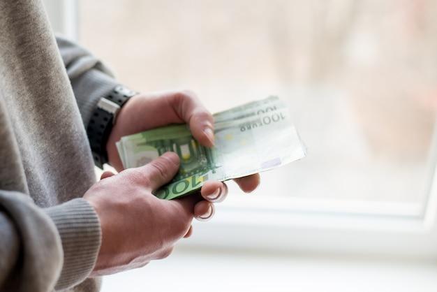 Euro geld. papier eurobankbiljetten in de hand van de man.