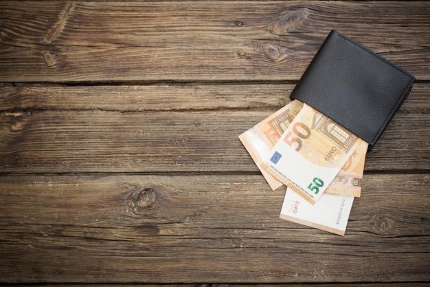 Euro in zwarte portemonnee op donkere houten achtergrond