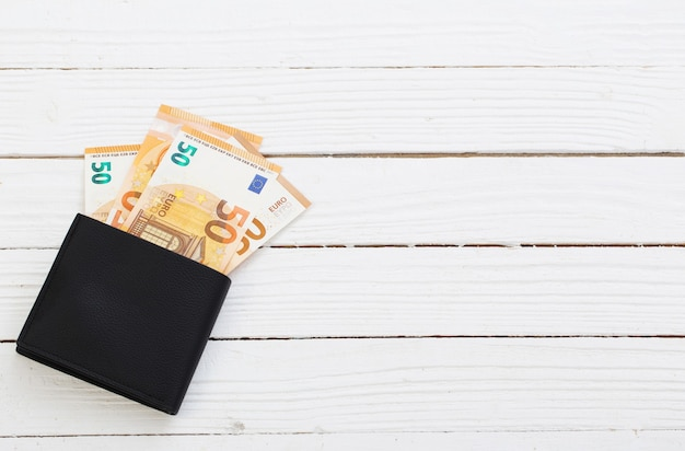Euro in zwarte portemonnee op witte houten achtergrond