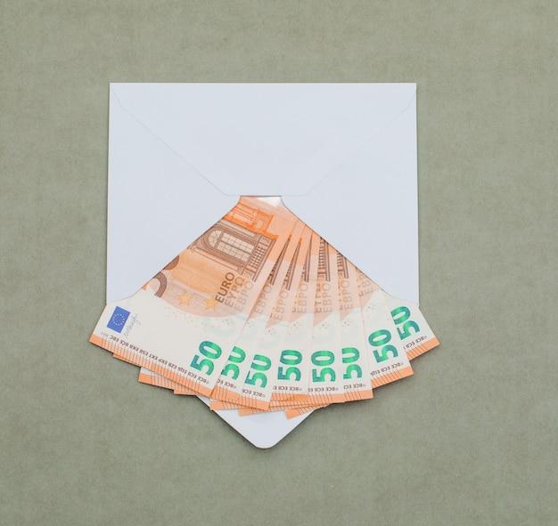 Euro rekeningen in envelop op groenachtig grijze tafel.