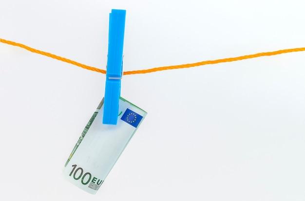 Eurobankbiljetten bevestigd met wasknijpers aan een touw op een witte geïsoleerde achtergrond
