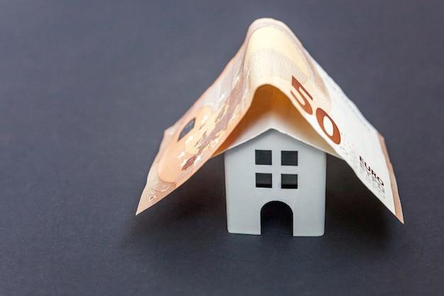 Eurobankbiljetten zoals dak op symbolisch klein stuk speelgoed huis