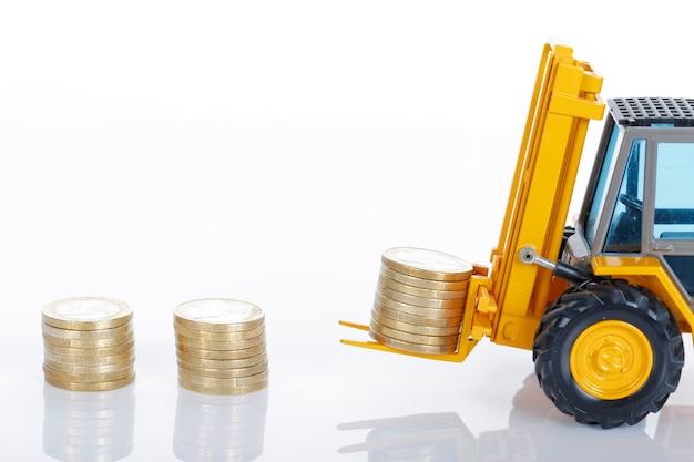 Euromunten geld en vorkheftruck geïsoleerd op witte ruimte