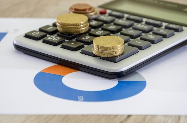 Euromunten met rekenmachine op de achtergrond van zakelijke grafieken en diagrammen close-up